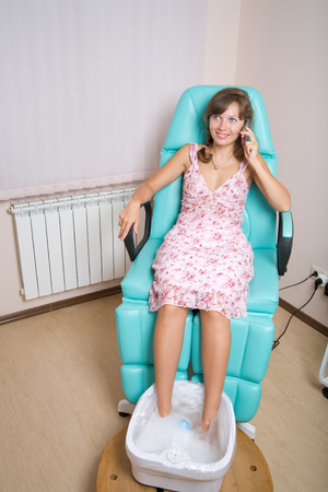 A young womant talking on mobile, while having pedicure Stock Photo - 1415530