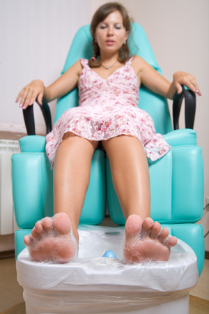A young woman having pedicure at beauty salon, focus on feet Stock Photo - 1415529