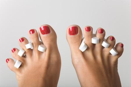pedicura: Los pies durante la pedicura, aislados en gris