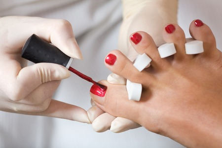 A photo of pedicure process - nail polishing.