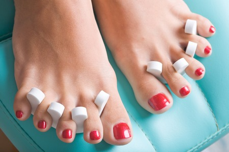 A pedicure process, focus on the left feet. Stock Photo