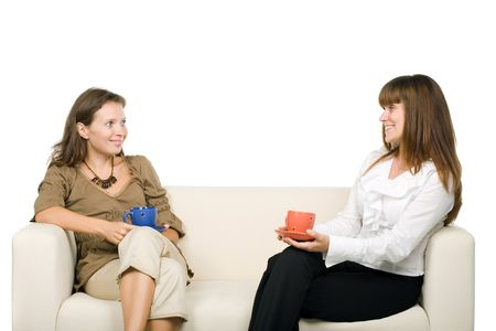 Two women chatting on the sofa, isolated