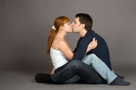 A photo of a young couple kissing, isolated on grey photo