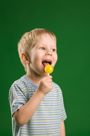 A photo of boy with lollipop on green photo