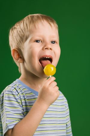 A photo of boy licking lollipop