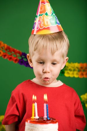 A boy trying to blow the candles on birthday cake photo