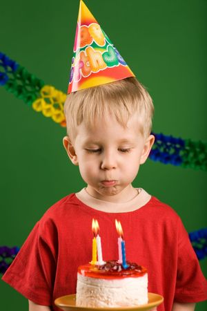 A boy preparing to blow the candles on cake photo