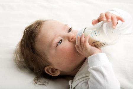 A baby eating milk from the bottle