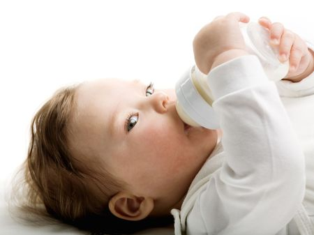 of a baby drinking milk from the bottle photo