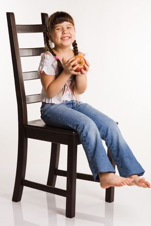 of a girl with apple, sitting on a chair photo
