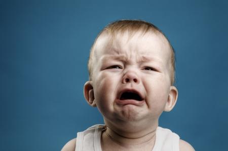 baby huilen: Foto van baby van negen maanden huilen, geïsoleerde Stockfoto
