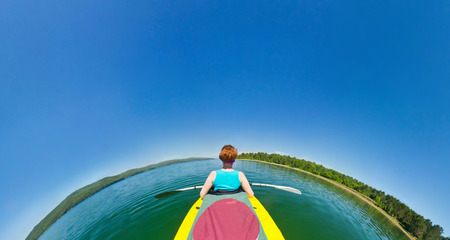 river fish: girl in a kayak floating down the river. fish eye