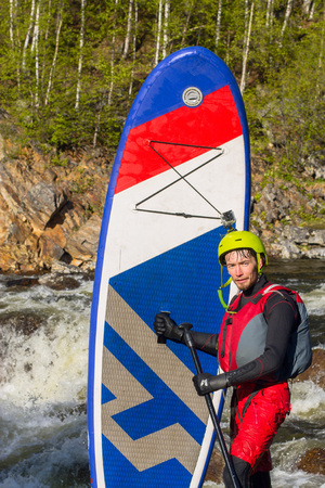 The man fell from SUP surfing on the rapids of the mountain river Stock Photo