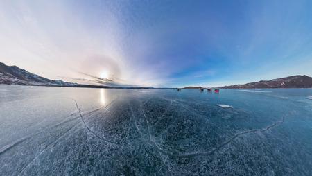 transition: Tourists make the transition ice on Lake Baikal ice at sunset. Stock Photo