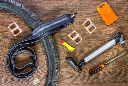 Kit de reparación de bicicletas, ruedas de la cámara en el fondo de madera Foto de archivo - 61193077