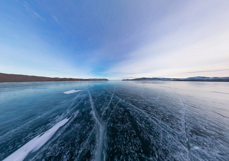 cracks in ice: Blue ice of Lake Baikal covered with cracks, cloudy weather sunset.