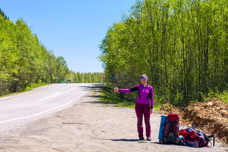 purple car: Girl in purple with backpacks hitchhike a car on the road