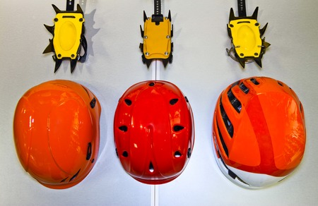 crampon: Climbing helmets and crampons on a gray background in  flat lay Stock Photo