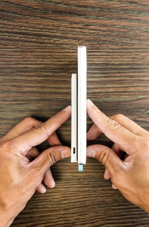 Smartphone charging with power bank on wood board background