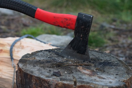 recursos naturales: Axe in billets, chainsaw lying on log Foto de archivo