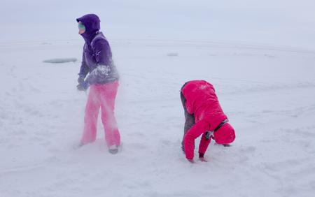 palle di neve: le donne svolgono nella neve durante la nevicata sul ghiaccio del lago Baikal.