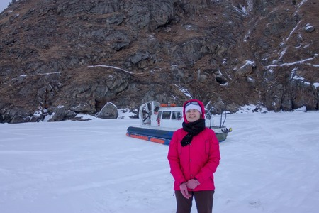 hovercraft: The girl standing next to a hovercraft at the rock on the Lake Baikal Stock Photo