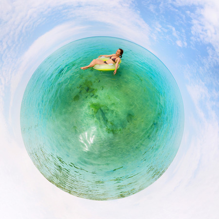 baical: Girl in inflatable ring floating in the azure water of Lake Baikal, the stereographic panorama