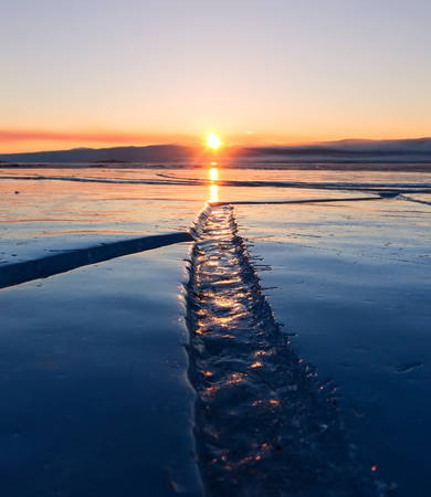 baical: Wide crack in the ice of Lake Baikal at sunset Stock Photo