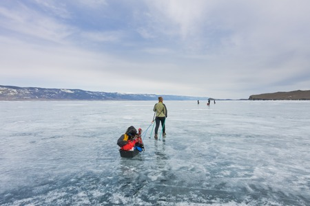 Girl with a sledge and trekking pole is on the blue ice of Baikal