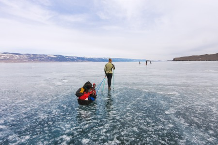 trekking pole: Girl with a sledge and trekking pole is on the blue ice of Baikal