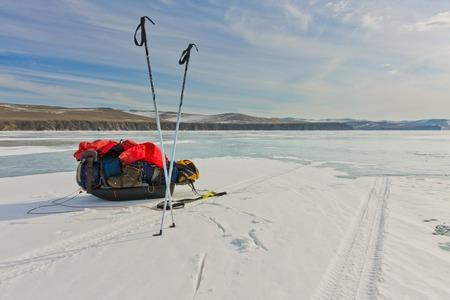 Ice sleigh and ski poles standing in the snow on the ice of Lake Baikal
