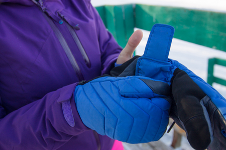 woman in a purple jacket dress blue mittens on his hands Stock Photo