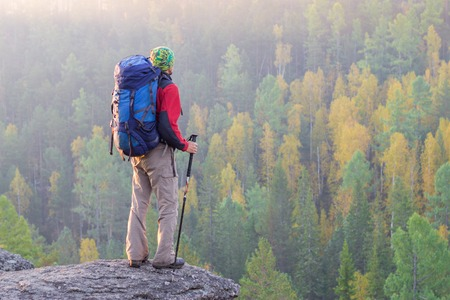 Man with backpack and trekking pole in bandana standing on a rock at dawn on a background autumn forest.