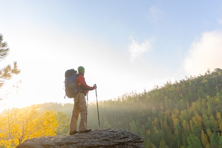 trekking pole: Man with backpack and trekking pole in bandana standing on a rock at dawn on a background autumn forest.