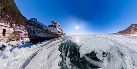 Old rusty ship on the coast of Lake Baikal among ice. Wide Panorama fish eye distortion Stock Photo