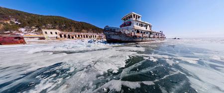 Wide panorama of the old rusty ship on the coast of Lake Baikal among ice Stock Photo
