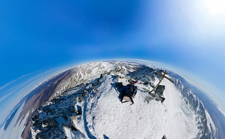Aerial survey the top of a snowy mountain on a sunny day at the wide angle fisheye. Stock Photo
