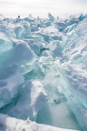 baical: Ice chunks of blue ice is covered with snow on a sunny day