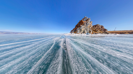 baical: Wide-angle view Shaman Rock or Cape Burhan on Olkhon Island in winter, surrounded by the blue ice of Lake Baikal with cracks.