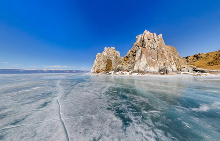 baical: Wide-angle view Shaman Rock or Cape Burhan on Olkhon Island in winter, surrounded by the blue ice of Lake Baikal with cracks Stock Photo