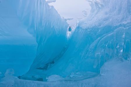 Girl standing on the wave of blue ice blocks at dusk. lake Baikal