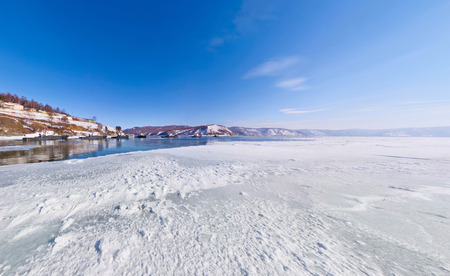The snow on the ice lake baikal at the pier from which the ship sails in Listvyanka, the Angara River estuary. Stock Photo