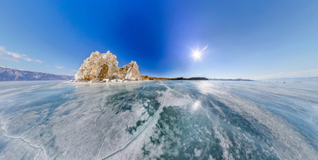 Wide-angle view Shaman Rock or Cape Burhan on Olkhon Island in winter, surrounded by the blue ice of Lake Baikal with cracks Stock Photo