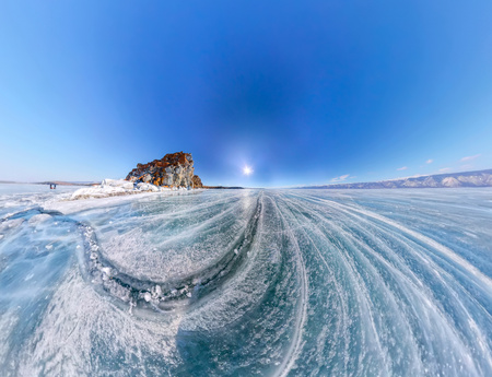 baical: Aerial panorama Shaman Rock or Cape Burhan on Olkhon Island in winter, surrounded by the blue ice of Lake Baikal with cracks