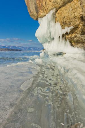 baical: a crack in the ice and ice sokui on the rock. Olkhon Island. Lake Baikal. Stock Photo