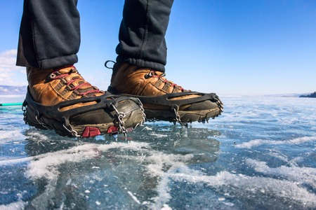 crampons: Human legs in hiking boot in ice crampons on the texture Baikal ice. Stock Photo