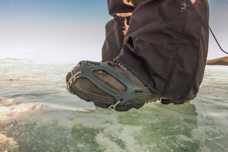 hiking boot: Human legs in hiking boot in ice crampons on the texture Baikal ice. Stock Photo