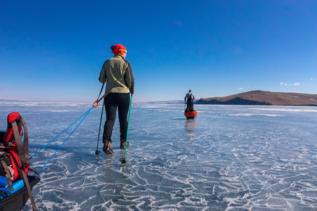 a woman and a man with a sledge and trekking pole is on the blue ice of Baikal Stock Photo