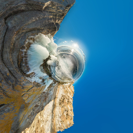 Rock on Olkhon covered with ice and icicles in Lake Baikal in winter. Polar little planet.