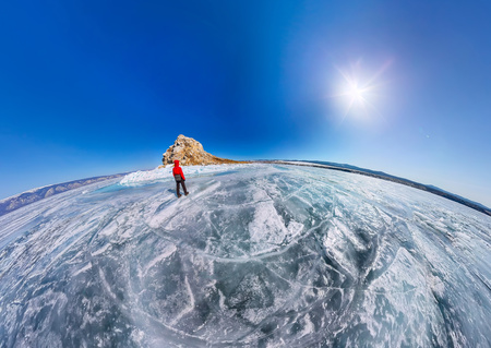 Wide aerial view of people at the rock on the ice of Lake Baikal
